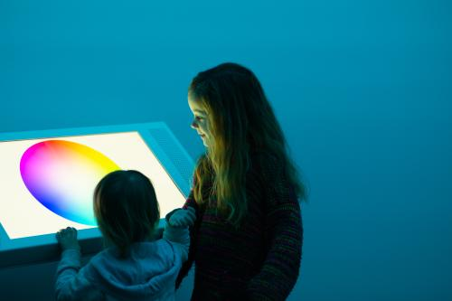 2 children looking at colourful lit panel with teal background