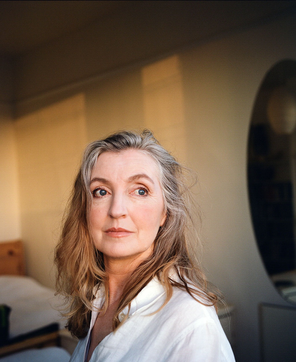 A headshot of activist Rebecca Solnit - a woman with flowing grey and brown hair, sat in the golden-hour light in a bedroom